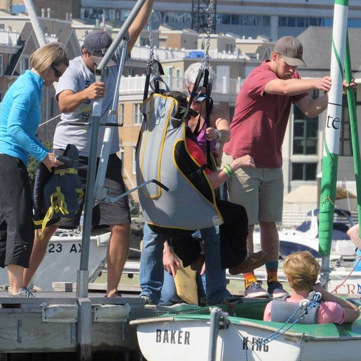 Volunteers assist with a hoyer lift transfer into a Hansa/Access dinghy