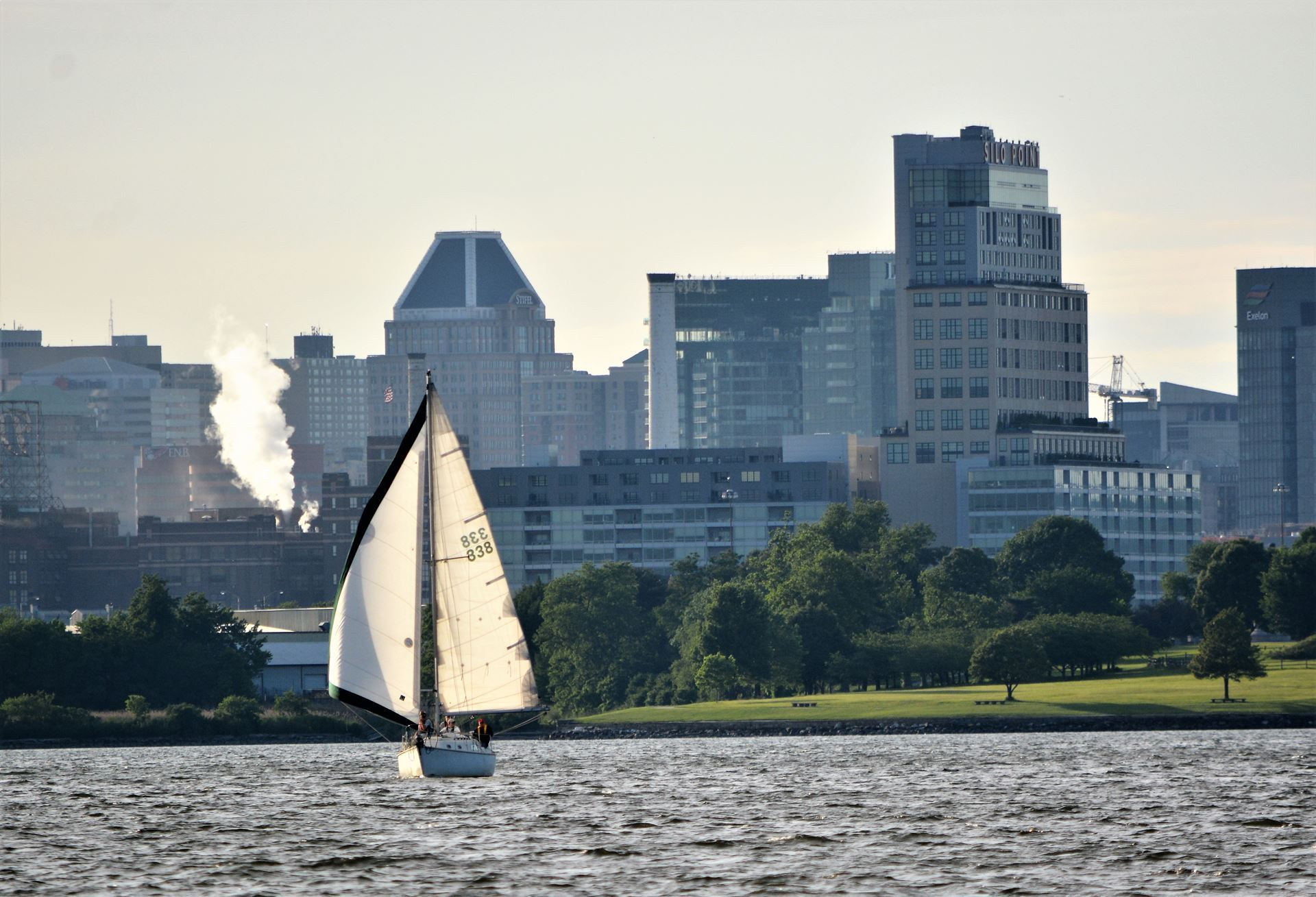 SPRITE sails past Fort McHenry for BCYA racing at Sunset with skyscrapers in background